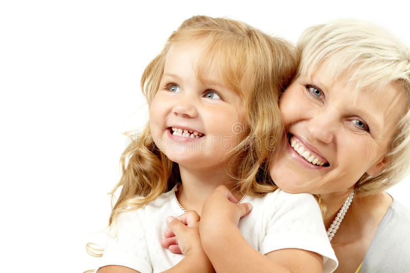 Happy grandmother. Embracing her granddaughter and looking at camera royalty free stock photography