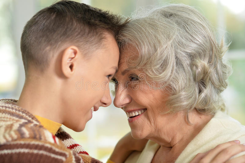 Happy grandmother and grandson. Portrait of Happy grandmother and her teen grandson look at each other stock photos
