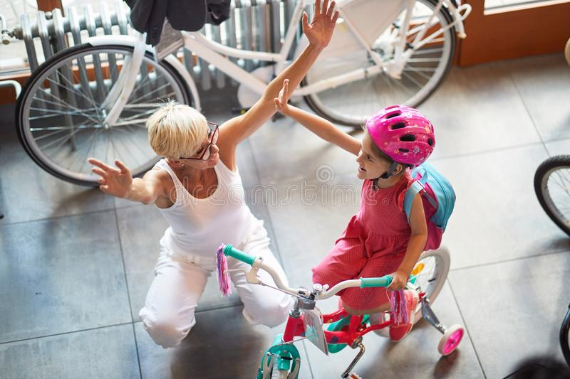 Happy grandmother with child buying new bicycle. Happy grandmother with little child buying new bicycle royalty free stock photography