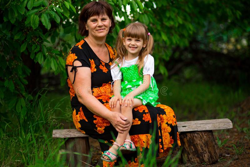 Happy grandmother and little granddaughter sitting in park. Happy grandmother and little granddaughter sitting in summer park stock images