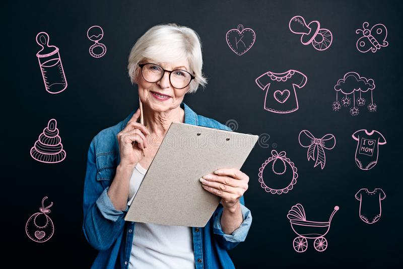 Happy grandmother making a list before going to a birthday party royalty free stock photo