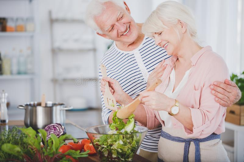 Happy grandmother mixing salad stock photo