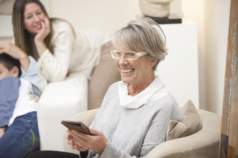 Happy grandmother with mobile phone and family at home stock image