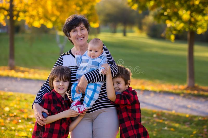 Happy grandmother in the park with her three grandsons royalty free stock photos
