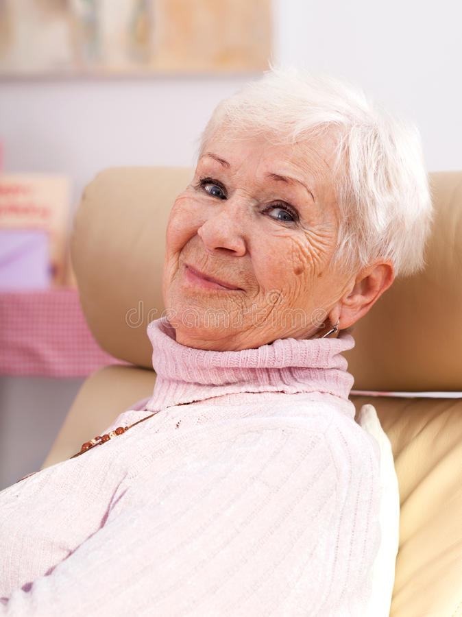 Happy grandmother smiling. A closeup of a happy grey grandmother with a smile stock photos