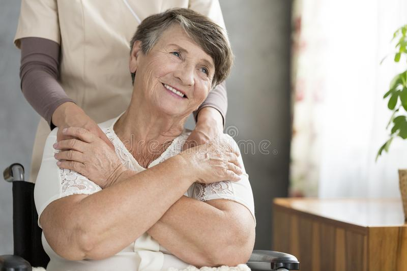Happy grandmother supported by nurse royalty free stock images