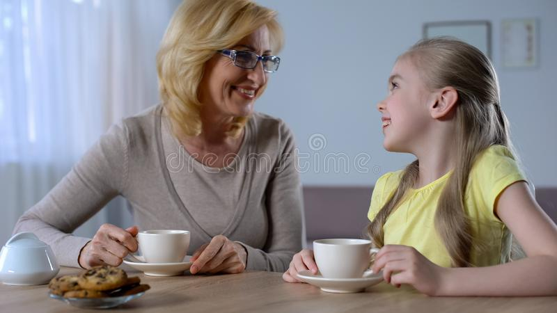 Happy grandmother talking and drinking tea with little cute granddaughter, love stock image