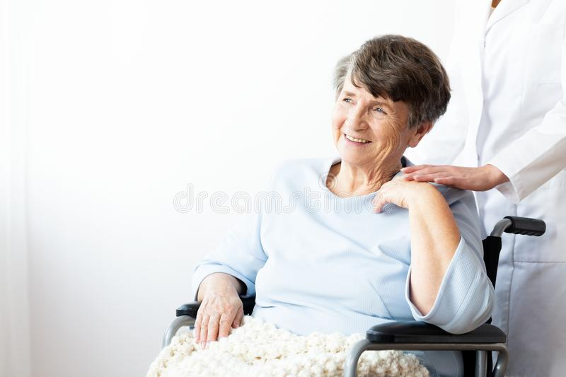 Happy grandmother in a wheelchair and caregiver supporting her. royalty free stock photo