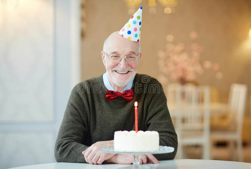 Happy Grandpa on Birthday n. Portrait of happy old man smiling to camera while sitting at table with birthday cake and wearing party hat stock photography