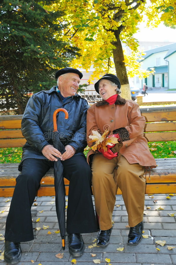 Happy grandparent on bench. In park royalty free stock photo