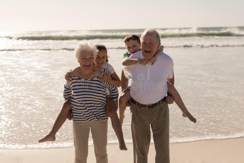 Happy grandparents giving piggyback to grandchildren on beach royalty free stock image