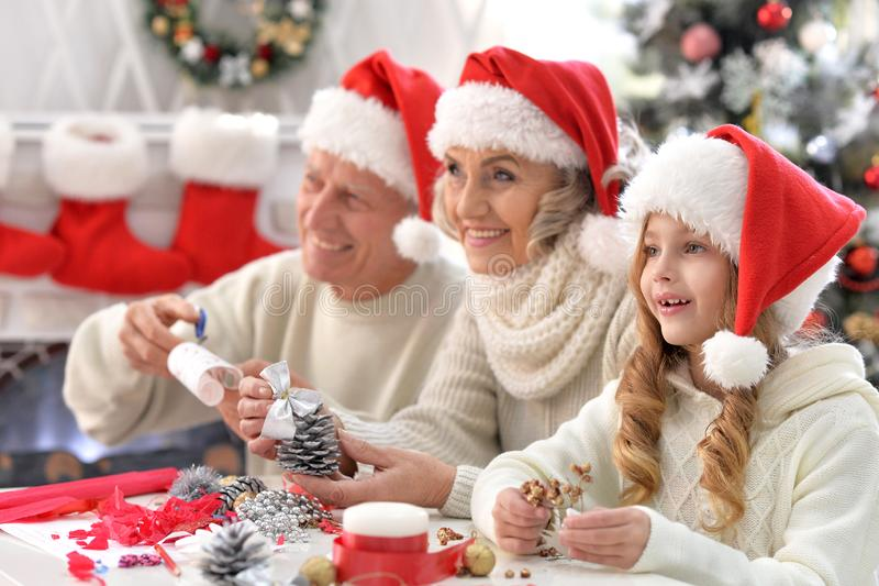 Happy grandparents with grandchild preparing for Christmas together royalty free stock photography