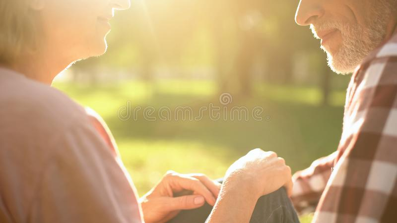 Happy grandparents looking at each other with love, resting on grass in park royalty free stock image