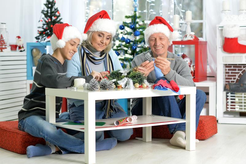 Portraint of grandparents with boy preparing for Christmas. Happy grandparents with their teen grandson preparing for Christmas at home royalty free stock photography