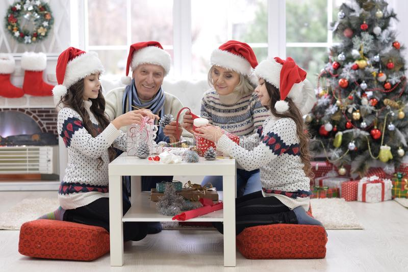 Happy grandparents with twin girls preparing for Christmas at home royalty free stock photo