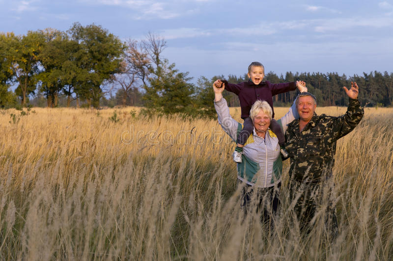 Happy grandson with grandfather and grandmother royalty free stock photography