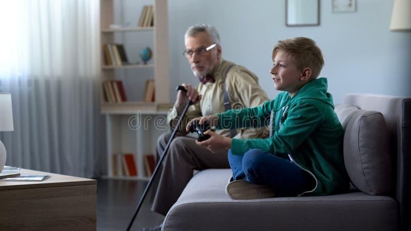 Happy grandson playing video game, upset grandpa sitting aside, generation gap stock photo