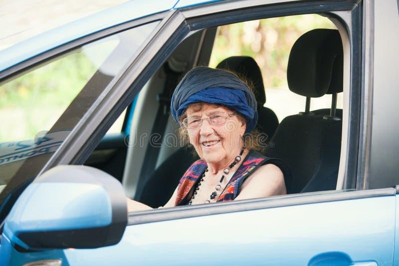 Happy granny at car. Old woman driving. Seniors royalty free stock photography