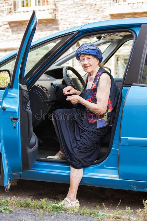 Happy granny at car. Old woman driving. Seniors stock image