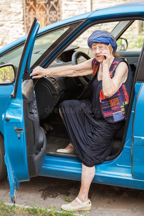 Happy granny at car. Old woman driving. Seniors royalty free stock images