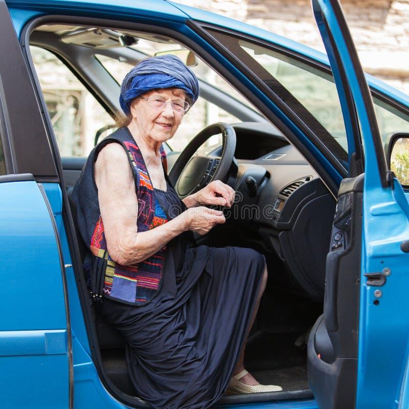 Happy granny at car. Old woman driving. Seniors stock photo