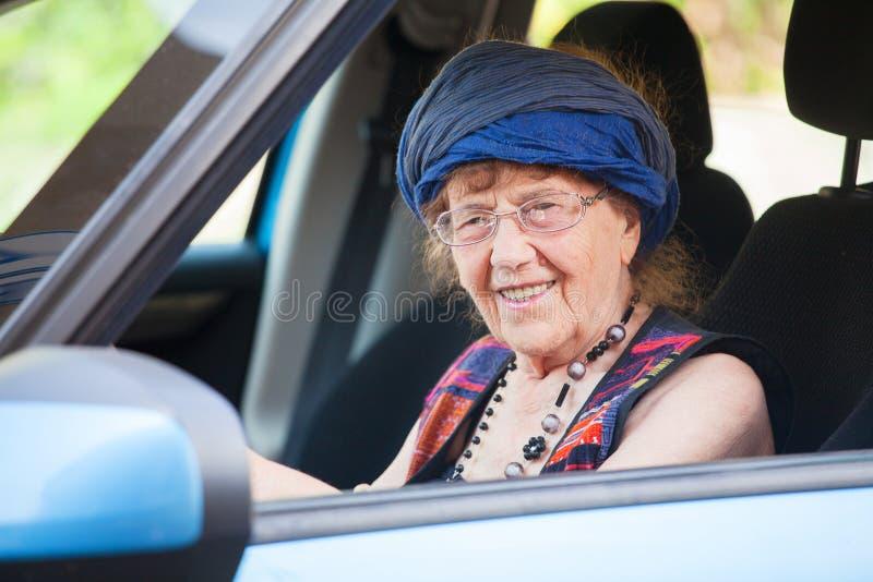 Happy granny at car. Old woman driving. Seniors stock photography