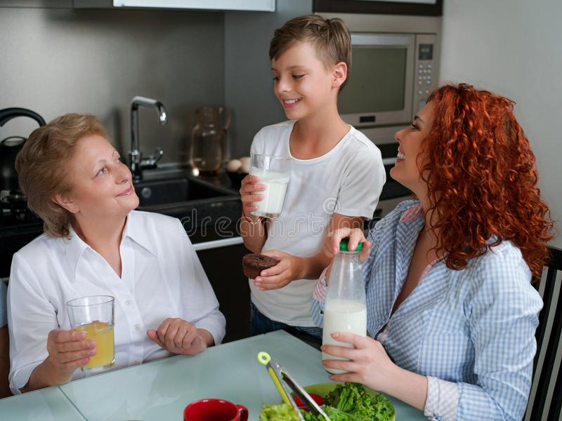 Happy granny drinking juice with children in the kitchen stock photography