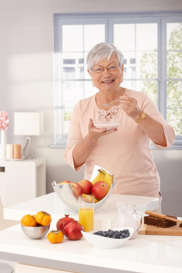 Happy granny eating breakfast cereal. Happy grandmother eating breakfast cereal by kitchen counter full of fruits royalty free stock photo