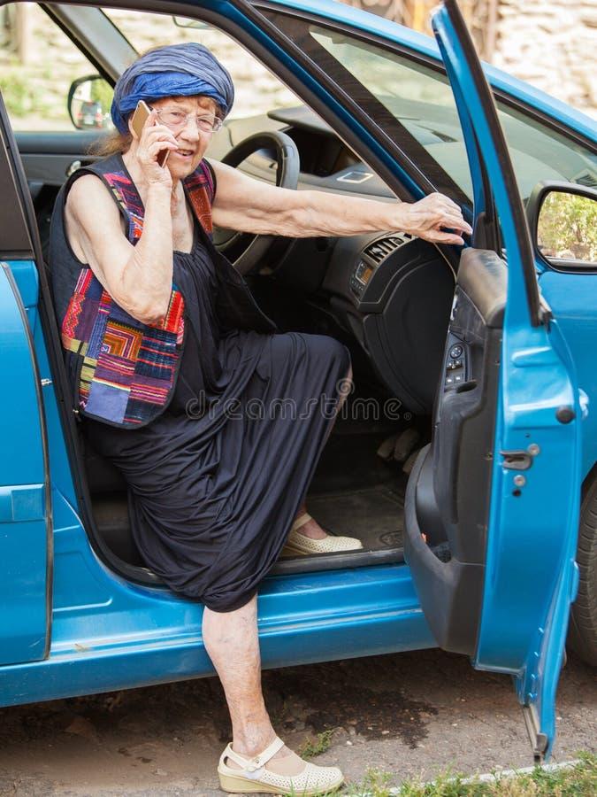 Happy granny woman at car. Happy granny at car. Old woman driving. Seniors stock photography