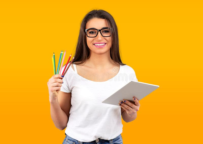 Happy graphic designer woman with colorful crayons and modern tablet computer royalty free stock images