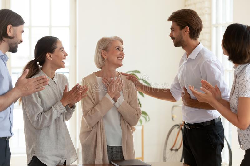 Happy old female employee get appreciated by boss and team. Happy grateful old middle aged female employee get promoted rewarded by boss and multiethnic team royalty free stock photo