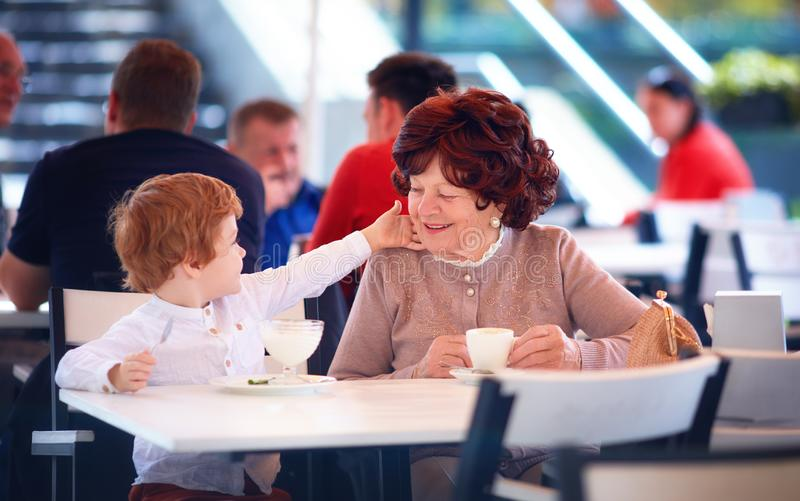 Happy great-grandmother having fun, sitting in summer cafe with her great grandson, sweet treats royalty free stock photos
