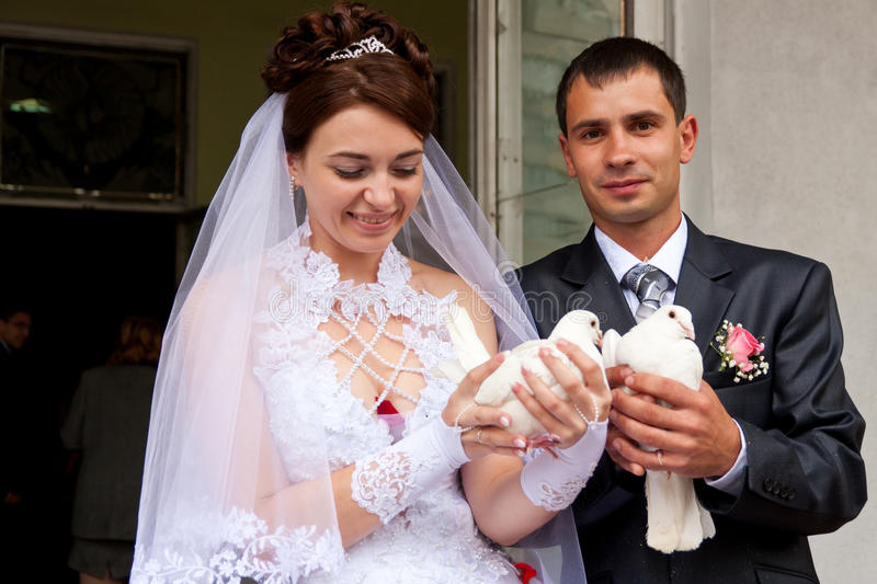 Happy groom and bride holding wedding pigeons royalty free stock photo