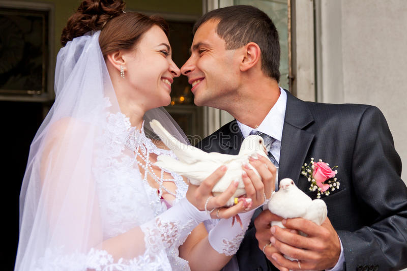 Happy groom and bride holding wedding pigeons. In hands royalty free stock photos