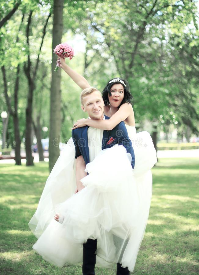 Happy groom carrying his bride in his arms royalty free stock photo