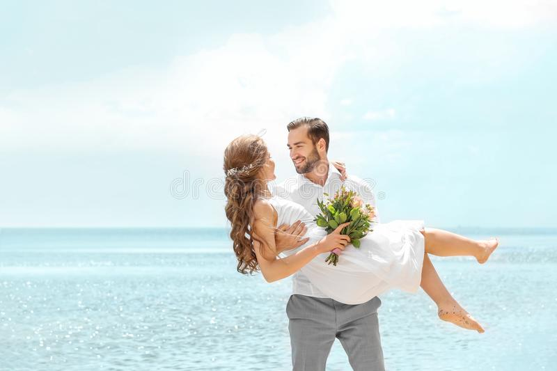 Happy groom holding bride in his arms stock images
