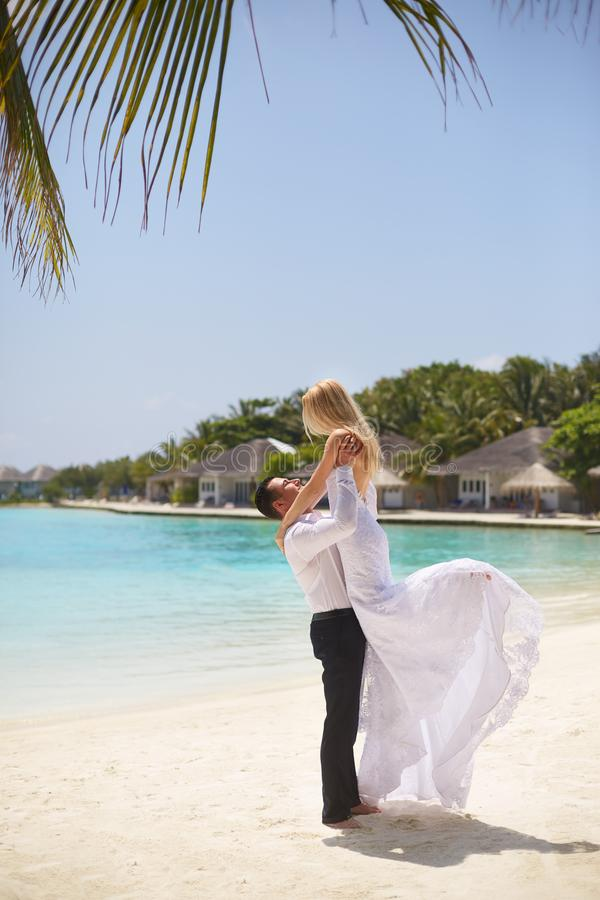 Happy groom holds bride on his hands under wedding ceremony arch on tropical island beach on Maldives. Turquoise ocean stock photo