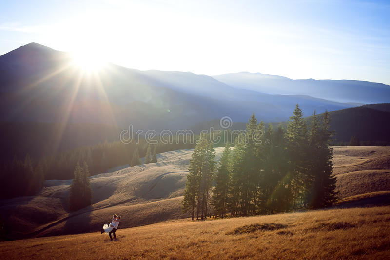 Happy groom holds in hands his beautiful bride. Wonderful mountains landscape stock images
