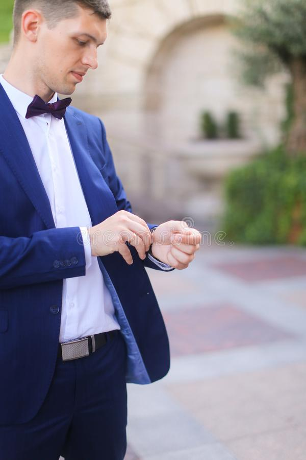 Happy groom waiting for bridea and looking at watch. royalty free stock images