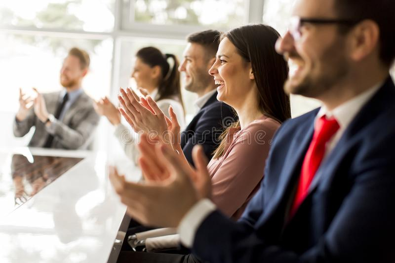 Happy group of businesspeople clapping in office stock image
