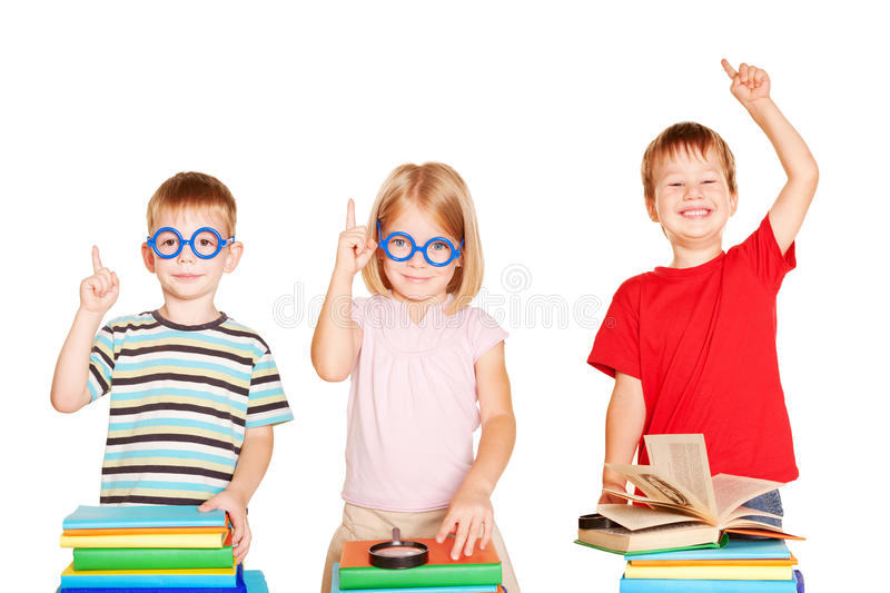 Happy group of children in a classroom with books. royalty free stock image