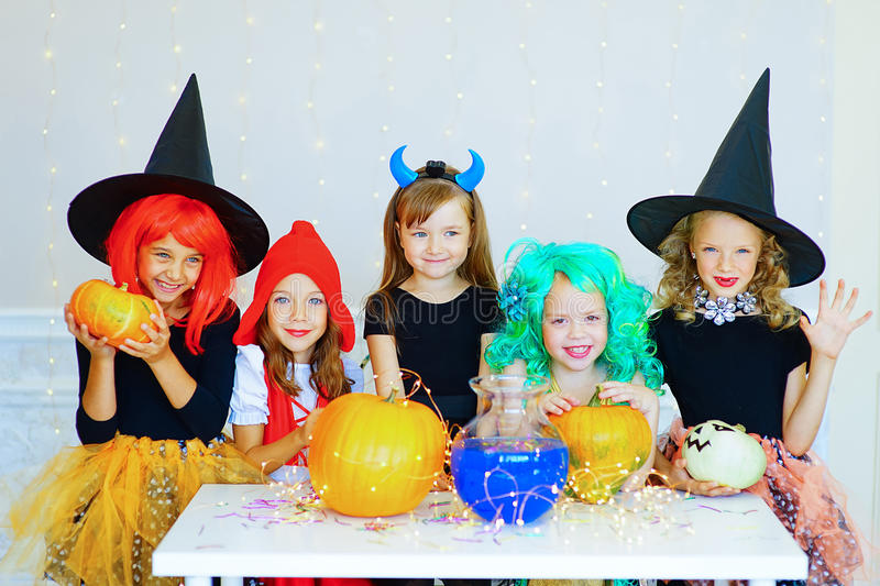 Happy group of children in costumes during Halloween party. Playing around the table with pumpkins and bottle of potion royalty free stock photography