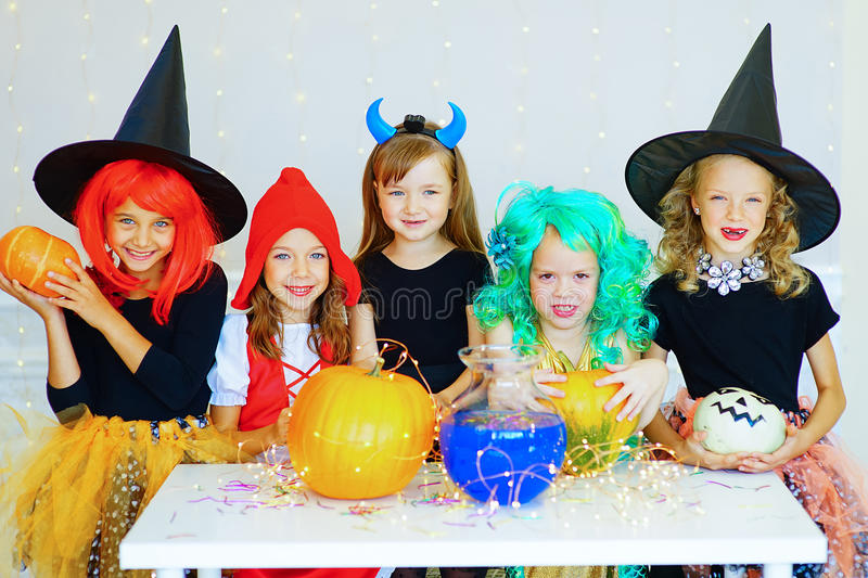 Happy group of children in costumes during Halloween party. Playing around the table with pumpkins and bottle of potion stock photos