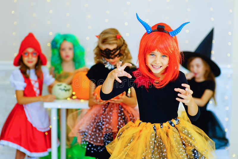 Happy group of children in costumes during Halloween party. Playing around the table with pumpkins and bottle of potion stock photo