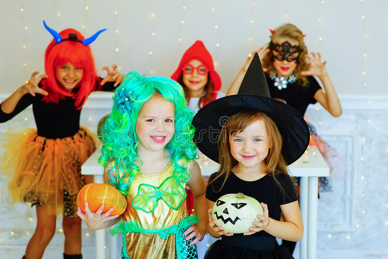 Happy group of children in costumes during Halloween party. Playing around the table with pumpkins and bottle of potion stock photography