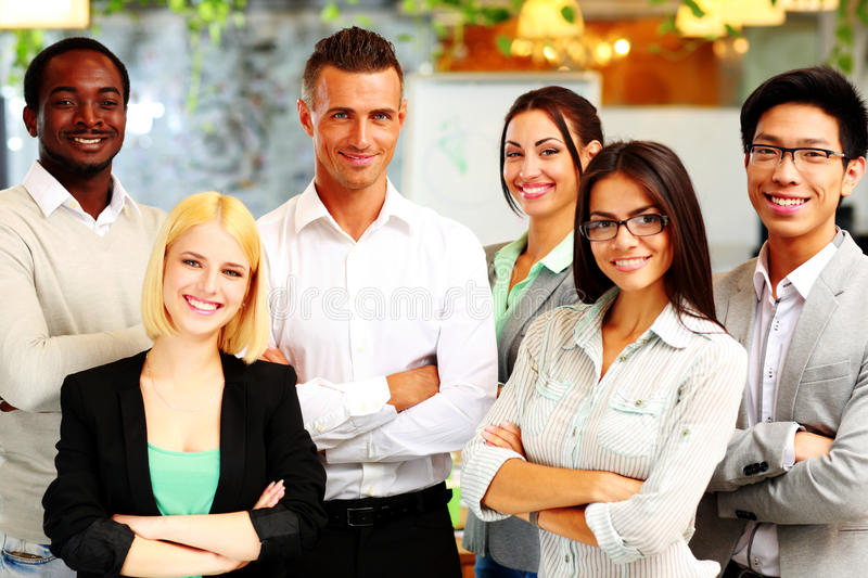 Happy group of co-workers standing. In office royalty free stock photos