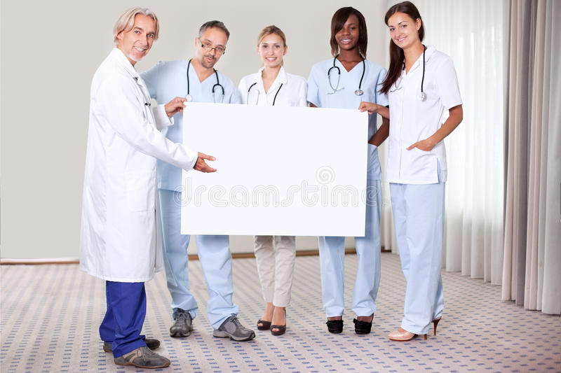 Happy group of doctors holding a blank placard stock photography