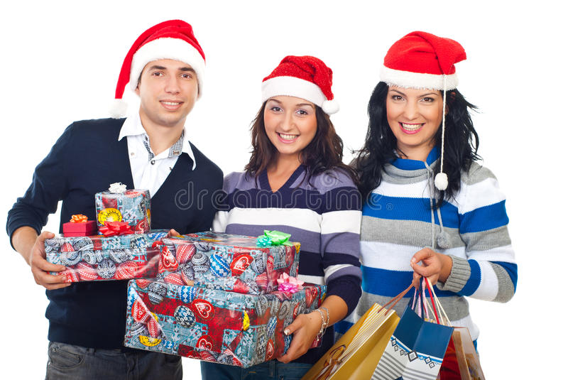 Happy group of friends with Christmas gifts. Happy group of friends with Santa hats standing in a row and holding Christmas gifts,bags and boxes isolated on stock photos