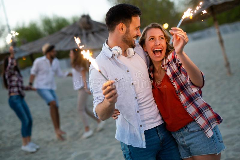 Happy group of friends lighting sparklers and enjoying freedom stock image