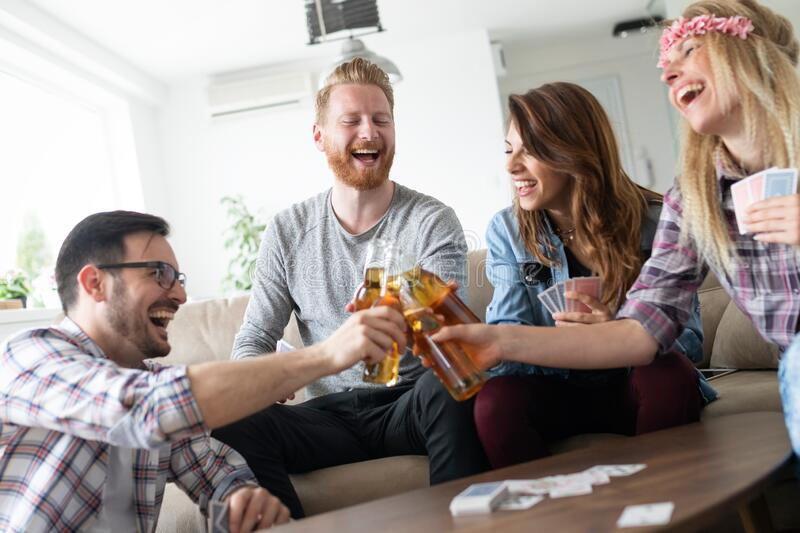 Group of happy friends playing cards and drinking royalty free stock photo